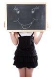 女孩在与微笑图象的一个黑板之后隐藏了 免版税库存照片
