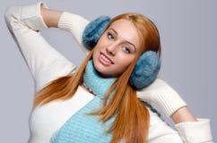 女孩在与手套、围巾和耳朵笨拙的人的冬天穿戴了 免版税库存照片