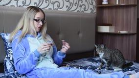 女孩在与早晨吃点心的一只猫的床上,看膝上型计算机 股票录像