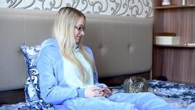 女孩在与早晨吃点心的一只猫的床上,看膝上型计算机 股票视频