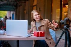 女孩在与膝上型计算机和礼物盒的一个咖啡馆坐,吃巧克力点心并且为照相 库存图片