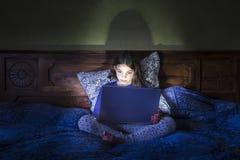 女孩在与膝上型计算机,发光的光的床上 图库摄影