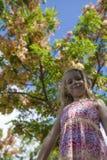 女孩在与花微笑的结构树下 免版税库存照片