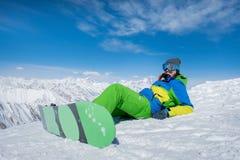 女孩在与雪板板的雪说谎 冬天 mo 免版税图库摄影