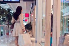 女孩在与购物袋的购物中心 免版税库存图片