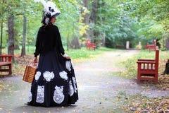 女孩在与valise的减速火箭的礼服18世纪在公园 免版税库存照片