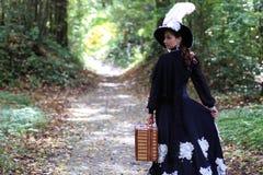 女孩在与valise的减速火箭的礼服18世纪在公园 库存照片