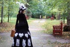 女孩在与valise的减速火箭的礼服18世纪在公园 免版税库存图片