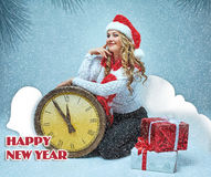 女孩在举行与圣诞节装饰的圣诞老人帽子穿戴了 免版税图库摄影