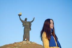 女孩在乌克兰全国颜色穿戴了反对蓝天 库存照片