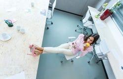 女孩在书桌上把她的脚放在办公室 库存图片