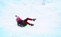 女孩在从冰幻灯片的一张幻灯片飞行 免版税库存照片