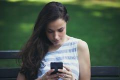 女孩在使用智能手机的城市公园 免版税库存照片
