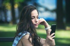 女孩在使用智能手机的城市公园 库存图片
