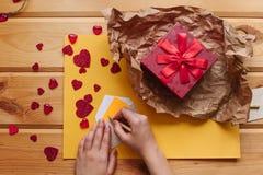 女孩在信封写一封信并且投入它 其次在一个美丽的红色箱子的一件手工制造礼物包扎与丝带 免版税图库摄影