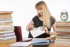 女孩在信封投入金钱贿赂检查的老师 库存图片