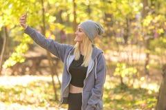 女孩在做selfie的森林里 免版税库存图片