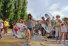 女孩在儿童保护天做用两条棍子和螺纹创造的大肥皂泡在伏尔加格勒 库存图片