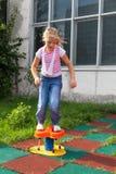 女孩在儿童操场的骑马乘驾 免版税库存照片