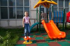 女孩在儿童操场的骑马乘驾 免版税库存图片