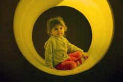 女孩在儿童` s操场喜欢上升通过一个隧道 免版税库存图片