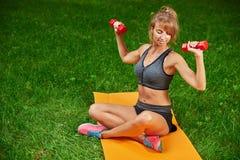 女孩在公园和参与与哑铃和席子的各种各样的锻炼 免版税图库摄影