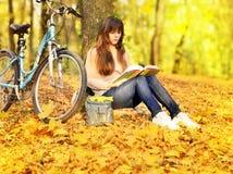 女孩在公园和自行车的读一本书 库存照片