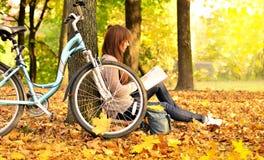 女孩在公园和自行车的读一本书 免版税库存照片