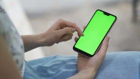 女孩在公园在她的手上拿着一个智能手机并且移动新闻 女孩在人脉沟通 股票录像