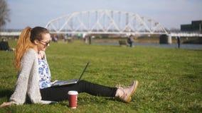 女孩在公园在谈话的草坐视频通信 学生,自由职业者,微笑并且笑 Peper杯子co 股票视频