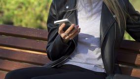 女孩在公园坐并且使用她的智能手机 影视素材