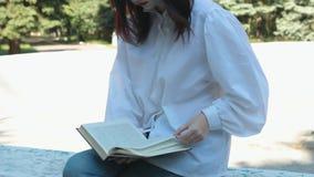 女孩在公园坐并且读一本书 股票录像