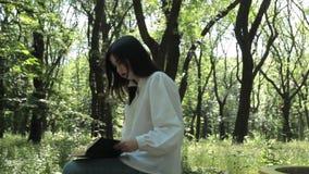 女孩在公园坐并且读一本书 股票视频
