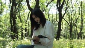 女孩在公园坐并且读一本书 影视素材