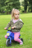 女孩在公园坐摩托车 免版税图库摄影