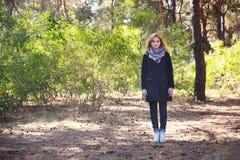 女孩在公园站立在一个晴天 免版税库存照片