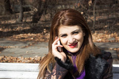 女孩在公园谈话在电话 免版税库存图片