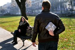 女孩在公园,接近与礼物的男朋友坐 免版税图库摄影