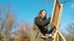 女孩在公园画一张图片 股票视频