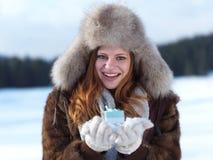 女孩在冬天场面和雪画象有礼物的在backgron的 库存图片