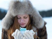 女孩在冬天场面和雪画象有礼物的在backgron的 库存照片