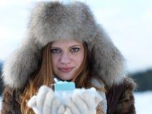 女孩在冬天场面和雪画象有礼物的在backgron的 免版税图库摄影