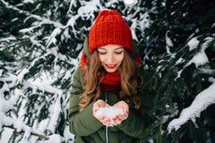 女孩在冬天多雪的森林里在手上拿着雪 库存照片