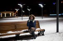 女孩在冬天夜坐长凳 库存照片