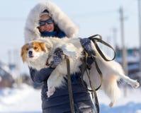 女孩在冬天拿着在她的胳膊的一条狗 库存图片