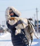 女孩在冬天拿着在她的胳膊的一条狗 免版税库存照片