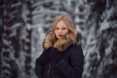 女孩在冬天森林走 免版税库存照片