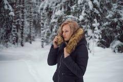 女孩在冬天森林走 库存照片