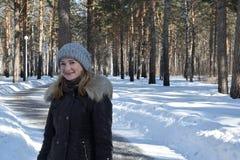 女孩在冬天森林里站立 免版税库存图片