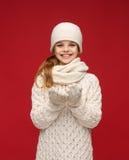 女孩在冬天穿衣与某事在棕榈 免版税图库摄影